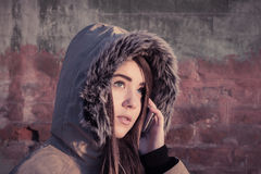 Portrait of a teenage girl outdoor wearing winter coat. Portrait close up of a teenage girl outdoor wearing winter coat with the faux - fur hood on and talking Royalty Free Stock Photography