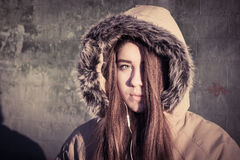 Portrait of a teenage girl outdoor wearing winter coat. Portrait close up of a teenage girl outdoor wearing winter coat with the faux - fur hood on. Toned effect Stock Photography