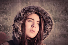 Portrait of a teenage girl outdoor wearing winter coat. Portrait close up of a teenage girl outdoor wearing winter coat with the faux - fur hood on. Toned effect Royalty Free Stock Images