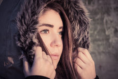 Portrait of a teenage girl outdoor wearing winter coat. Portrait close up of a teenage girl outdoor wearing winter coat with the faux - fur hood on. Toned effect Royalty Free Stock Photo