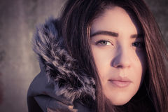 Portrait of a teenage girl outdoor wearing winter coat. Portrait close up of a teenage girl outdoor wearing winter coat with the faux - fur hood. Toned effect Stock Images