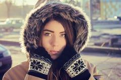 Portrait of a teenage girl outdoor wearing winter coat. Portrait close up  of a teenage girl outdoor wearing gloves and winter coat with the faux - fur hood on Royalty Free Stock Image