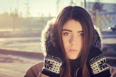 Portrait of a teenage girl outdoor wearing winter coat. Portrait close up  of a teenage girl outdoor wearing gloves and winter coat with the faux - fur hood on Royalty Free Stock Photo