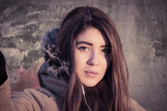Portrait of a teenage girl outdoor wearing winter coat. Portrait close up of a smiling teenage girl outdoor wearing winter coat with the faux - fur hood. Toned Stock Photos