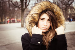 Portrait of a teenage girl outdoor. Wearing winter coat with the faux - fur hood on Royalty Free Stock Photo