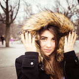 Portrait of a teenage girl outdoor. Wearing winter coat with the faux - fur hood on Royalty Free Stock Image