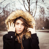 Portrait of a teenage girl outdoor. Wearing winter coat with the faux - fur hood on Stock Photography