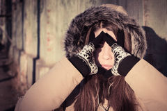 Portrait of a teenage girl outdoor wearing winter coat. With the faux - fur hood on and with hands covering her face from sunlight. Toned effect Royalty Free Stock Image