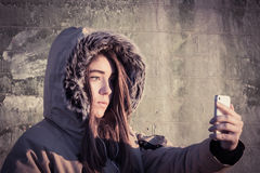 Portrait of a teenage girl outdoor wearing winter coat. With the faux - fur hood on and taking self portrait with her smart phone. Toned effect Royalty Free Stock Images