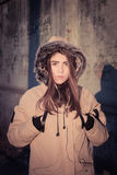Portrait of a teenage girl outdoor wearing winter coat. With the faux - fur hood on. Toned effect Stock Photography