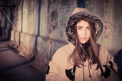 Portrait of a teenage girl outdoor wearing winter coat. With the faux - fur hood on. Toned effect Royalty Free Stock Photo