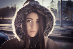 Portrait of a teenage girl outdoor wearing winter coat. With the faux - fur hood on. Toned effect Stock Photos