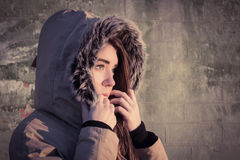 Portrait of a teenage girl outdoor wearing winter coat. With the faux - fur hood on. Toned effect Royalty Free Stock Photography