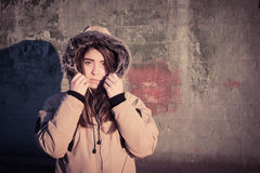Portrait of a teenage girl outdoor wearing winter coat. With the faux - fur hood on. Toned effect Stock Images
