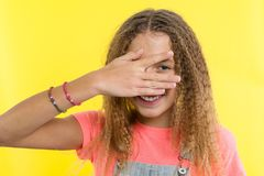 Portrait of teenage girl peeps through fingers. Yellow studio background stock photo