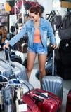 Portrait of teenage girl picking new big plastic luggage bag wit Royalty Free Stock Photography