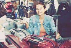 Portrait of teenage girl picking new big plastic luggage bag wit Stock Photos