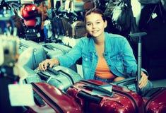 Portrait of teenage girl picking new big plastic luggage bag wit Stock Images