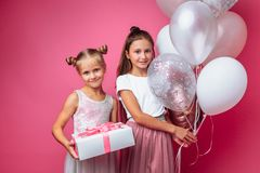 Portrait of a teenage girl on a pink background, with gifts, birthday concept, one gives another girl a gift royalty free stock photography