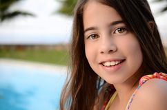 Portrait of a teenage girl by the pool. 11 year old girl enjoying the summer vacation by the pool on the Greek island of Crete Royalty Free Stock Image