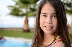 Portrait of a teenage girl by the pool. 11 year old girl enjoying the summer vacation by the pool on the Greek island of Crete Royalty Free Stock Images