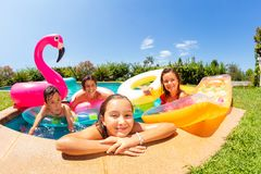 Happy girl relaxing with friends in outdoor pool royalty free stock images