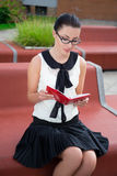 Portrait of teenage girl in school uniform sitting on bench and Royalty Free Stock Image