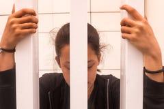 Teenage girl looking worried as she grips bars stock images