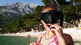Teenage girl putting on diving equipment. Portrait of teenage girl standing in shallow water of sea and putting on diving mask and snorkel with mountains on stock footage