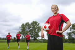 Portrait of teenage girl in uniform holding soccer ball Royalty Free Stock Images