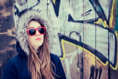 Portrait of a teenage girl wearing red sunglasses. And coat hood royalty free stock photography