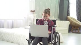 Portrait of a teenage girl in a wheelchair, uses a laptop, at home in the bedroom