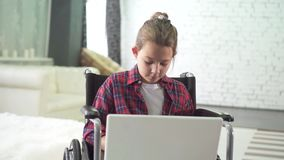 Portrait of a teenage girl in a wheelchair, using a laptop and the Internet social networks
