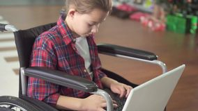 Portrait of a teenage girl in a wheelchair, using a laptop and the Internet social networks slow mo