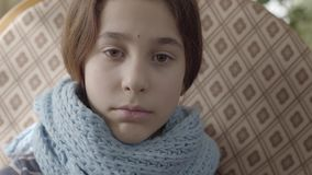 Portrait of teenage girl wrapped in warm scarf. The girl feels bad, she is ill and has a fever. Concept of healthcare stock footage