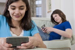 Portrait of a teenage girlfriends sending emails Stock Photography