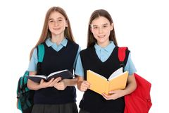 Portrait of teenage girls in school uniform with backpacks and books royalty free stock photos