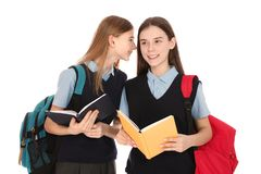 Portrait of teenage girls in school uniform with backpacks and books. On white background stock photos