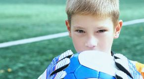 Portrait of teenage goal keeper holding ball on school soccer pitch. Portrait of goal keeper holding ball on school soccer pitch stock photo