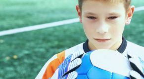 Portrait of teenage goal keeper holding ball on school soccer pitch. Portrait of goal keeper holding ball on school soccer pitch royalty free stock image