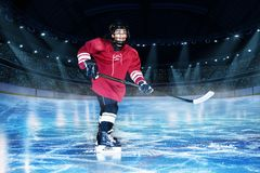 Hockey player with stick on the rink of ice arena. Portrait of teenage hockey player with stick on the spotlighted rink of ice arena royalty free stock photo