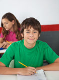 Portrait Of Teenage Male Student Sitting At Desk. With female classmate in background Stock Images