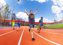 Portrait of teenage sprinter crossing finish line Royalty Free Stock Photography