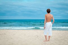Portrait of teenage standing on sand near sea Stock Photo