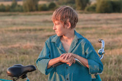 Portrait of teenager boy with bicycle at sunset Stock Images