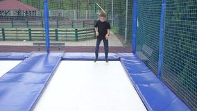 Teenager boy demonstrates how to do a somersault on a trampoline. Portrait teenager boy demonstrates how to do a somersault on a trampoline stock footage