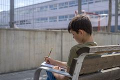 Portrait of a teenager boy sitting doing his homework. Portrait of a teenager boy sitting on a wood park bench doing his college homework and studying writing Stock Photos