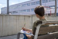 Portrait of a teenager boy sitting doing his homework. Portrait of a teenager boy sitting on a wood park bench doing his college homework and studying writing Royalty Free Stock Photos