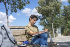 Portrait of a teenager boy sitting doing his homework. Portrait of a teenager boy sitting on a wood park bench doing his college homework and studying writing Royalty Free Stock Photo