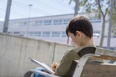 Portrait of a teenager boy sitting doing his homework. Portrait of a teenager boy sitting on a wood park bench doing his college homework and studying writing Stock Image